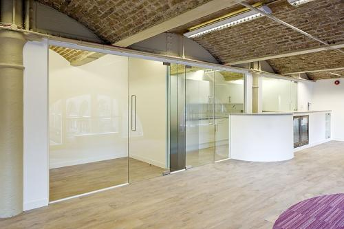 Frameless glass partition system with glass doors